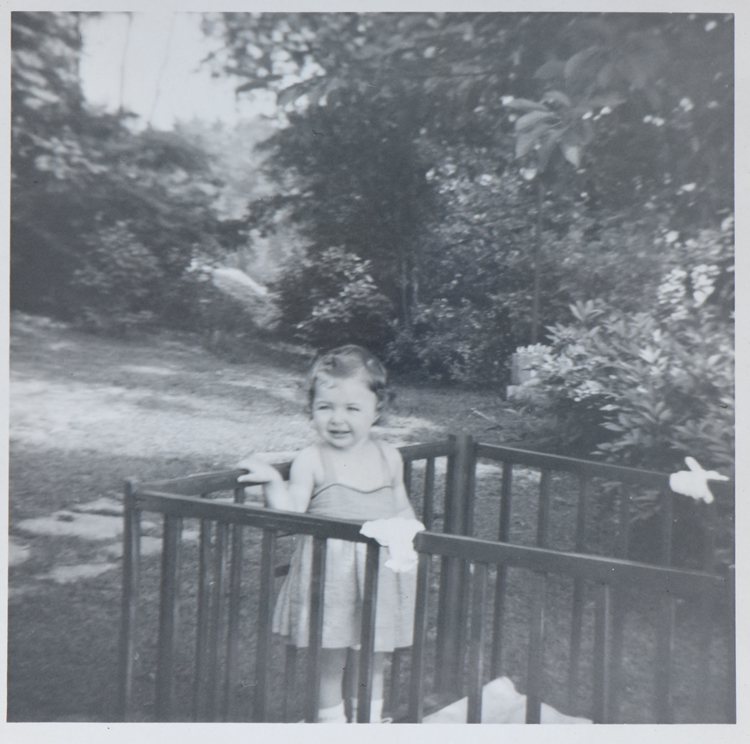 This is a photo of Nancy Martin from 1954 in her playpen set in the shade of a huge maple tree at her childhood home in West View. She loved the tree as a child and mourns its loss after being cut down by her mother.
