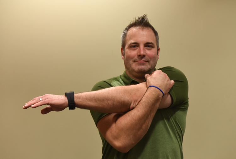Ryan Taucher, exercise physiologist for Excela Heath shows how to do a cross body shoulder stretch.