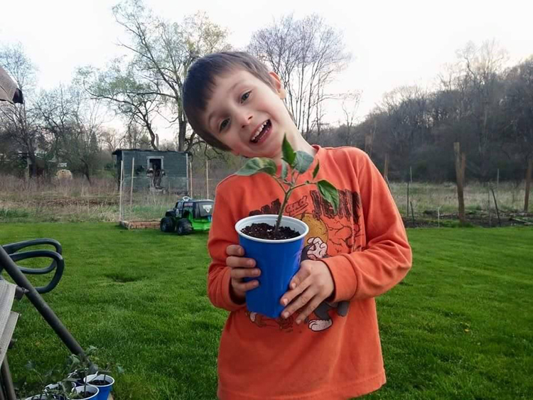 Matthew Goehring enjoys sharing his passion for gardening with his kids. His son Jacob, 6, is seen here holding a pepper plant ready to go into the garden.