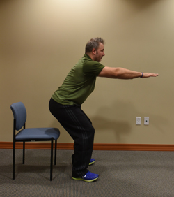 Ryan Taucher, exercise physiologist for Excela Heath shows how to do squats using a chair as a saftey so he doesn't go down too far.