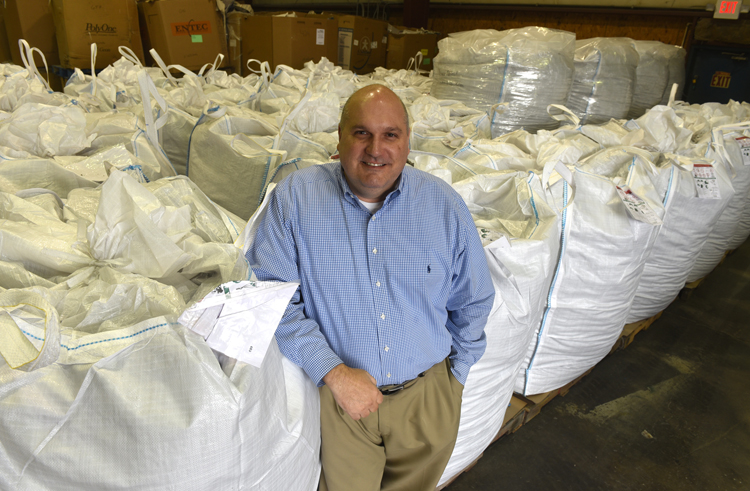 Brian Scott, CEO of Pitt Moss in Ambridge poses in the company's warehouse with bags of material used to make their product.