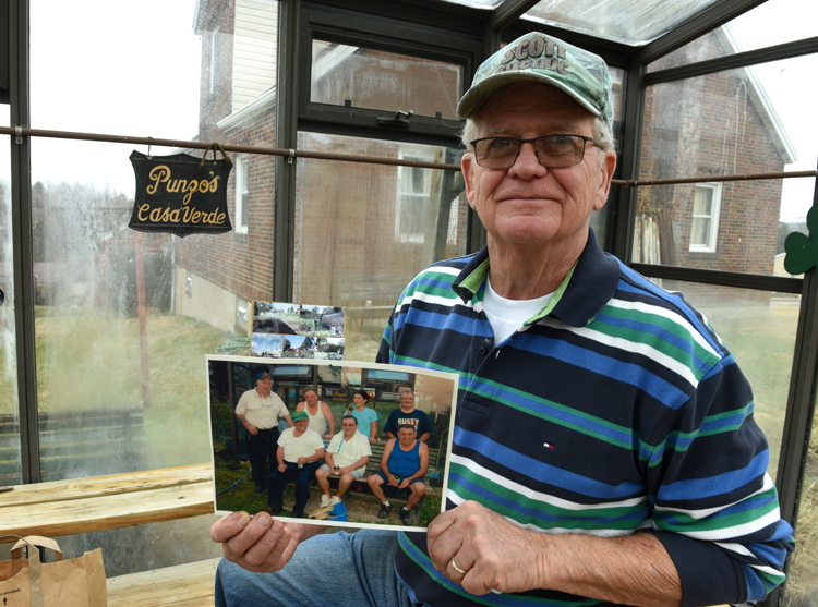 "John Wassel proudly shows of a photo of ""Uncle Punzo"" and the gang that worked in his large garden."