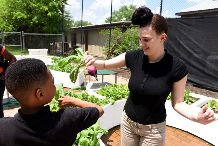 Dorian Cole, 11, (left) and Kylee Arlatta, 15, marvel at the size of the radishes they harvested out of the Learning Garden at Clayton Academy in Pittsburgh's Northside neighborhood. The garden is made possible through a partnership between Grow Pittsburgh and the national organization Big Green.