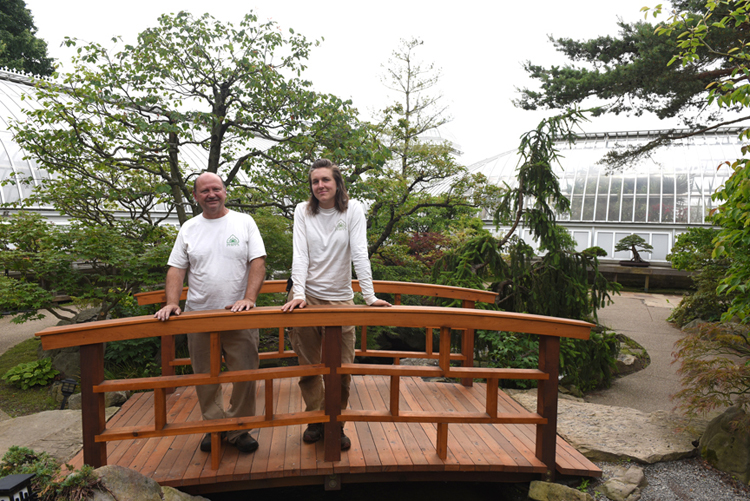 Kevin Haughey and Jessica Horenstein stand on the bridge in the recently refreshed Japanese Courtyard Garden at Phipps Conservatory and Botanical Gardens. Japanese landscape designer Hoichi Kurisu designed the garden in 1991 and then recently returned to tweak the garden with his team.