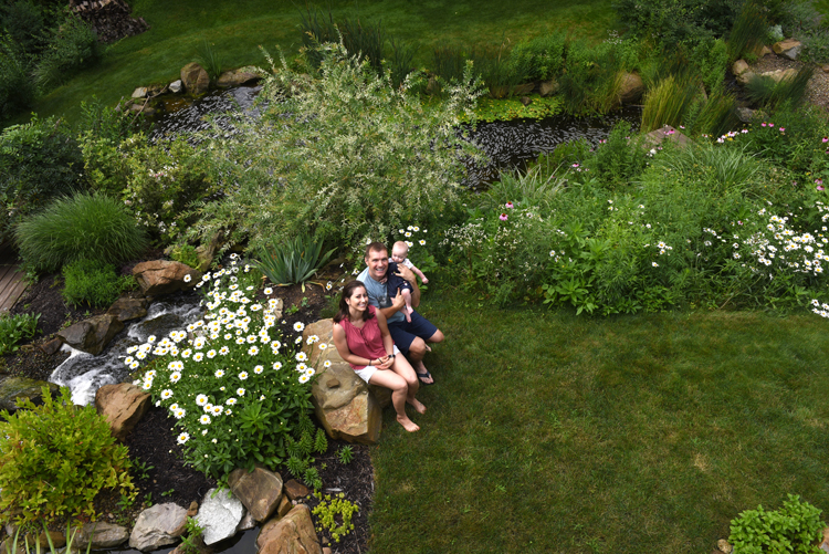 Scott and Catie Walsh of Sewickley Hills hold their seven month-old daughter Amara in the water garden that's part of the Wexford Pond Tour. The water garden is like a retreat for the young family.