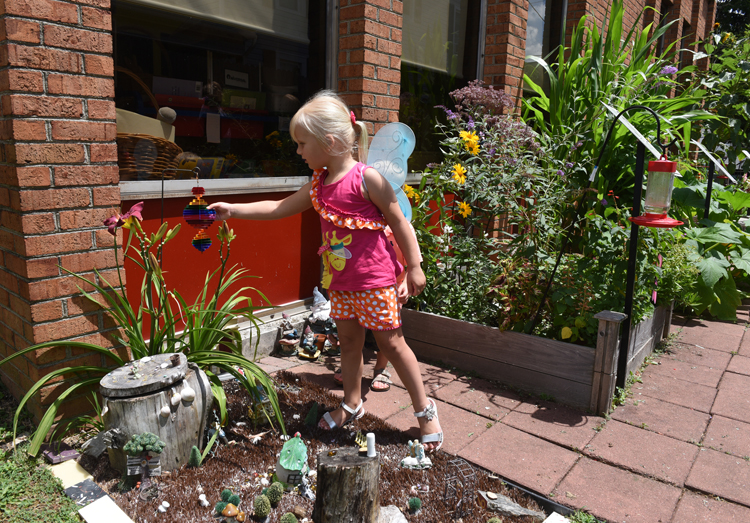 """Amaris Geer, 4, touches one of her favorite things in the fairy garden at Mount Pleasant Library, it's part of the Story Garden. She said of the whirlygig, """"sometimes I really, really, really like that thing over there."""""""