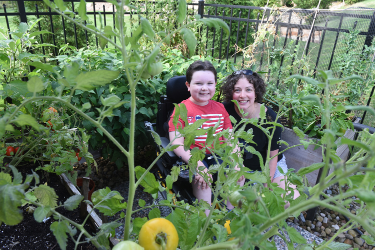 Reid Hall, 9, and his mother Jenny Hall enjoy their raised bed garden in Allison Park. Reid has spinal muscular atrophy, a genetic neuromuscular disorder. He enjoys being in the garden and loves the produce too.
