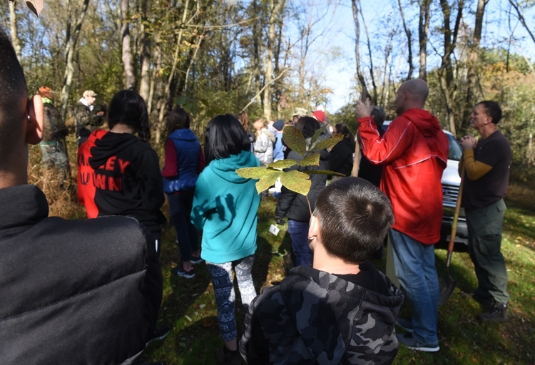 The crowd of volunteers and students from Ross Elementary listen to Joe Stavish, community eductaion coordinator for Tree Pittsburgh as part of a One Tree Per Child Pittsburgh event in Sangree Park in Ross.