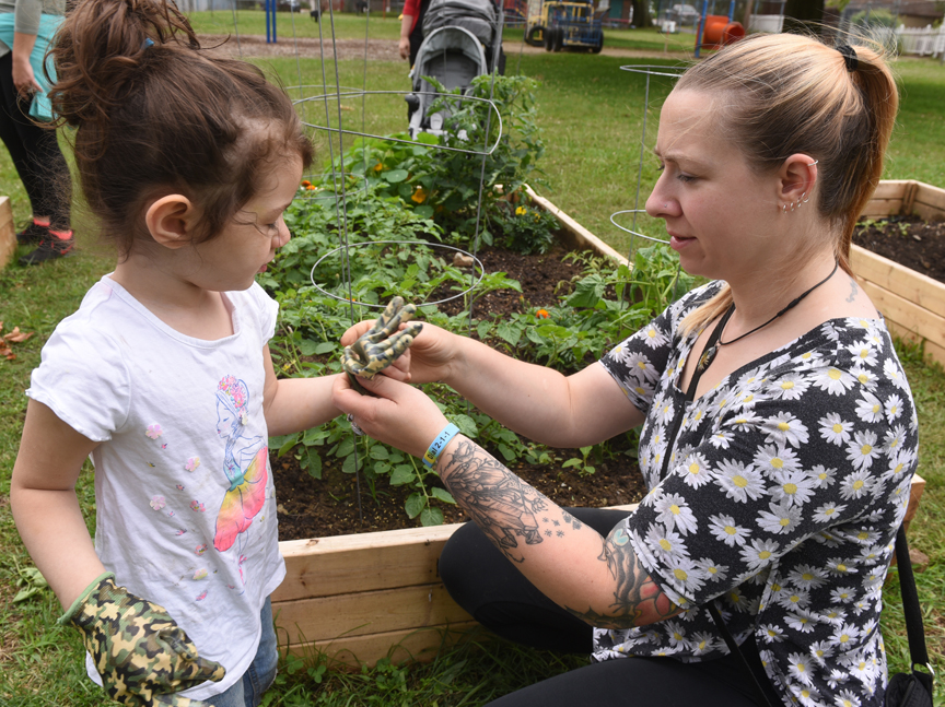 Rowan Roberto, 3, gets help putting on garden gloves from Chloe Kruse of the Vandergrift Parent Project in the children's garden located in the town's Franklin Park.