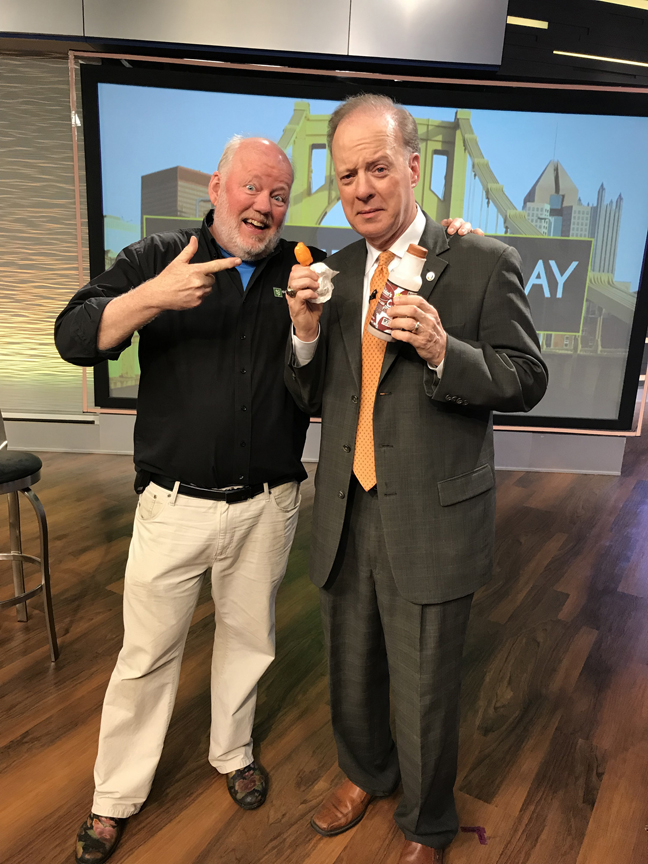Jon Burnett from KDKA-TV holds another habanero pepper and some much needed milk while recovering from eating a habanero pepper live on the air with Doug Oster during a retirement segment on Pittsburgh Today Live.