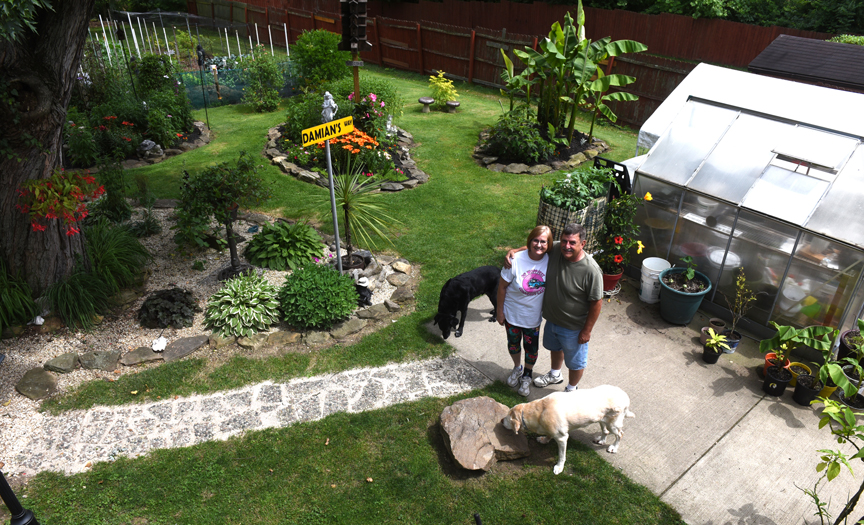 Damian and Gloria Ondo of Monroeville grow hardy bananas in their garden, seen here with their dogs Simba and Caesar. Besides bananas the couple grows lots of flowers and vegetables too.