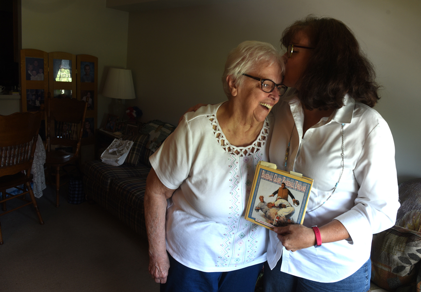 Dorothy Shillingburg gets a kiss from her neice Amy Wilkinson who is holding Herman Wigle's journal. He was Shillinburg's father and Wilkinson's grandfather. He was instrumental in teaching both about gardening and life.