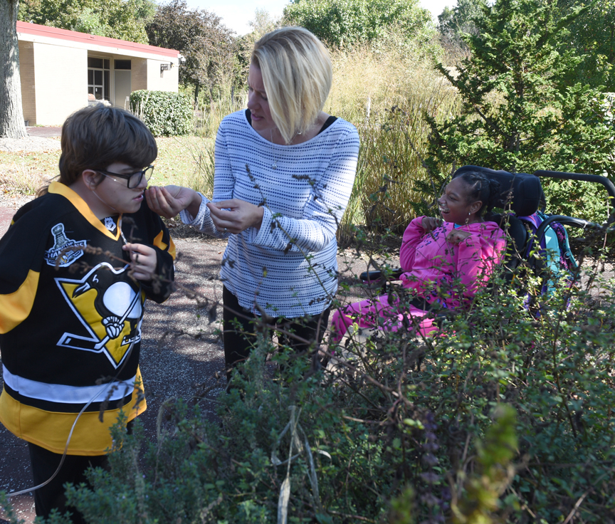 Cody Clegg, 13, (left) trys to identify an herb by its aroma. Suzanne Ambrose is the activities of daily living teacher at Pioneer Education Center in Pittsburgh. She and her students start seeds every year for the Sensory Garden at the school. To the right is Jordan Comans who harvested peppers with Ambrose and was also enjoying the aromatic herbs.