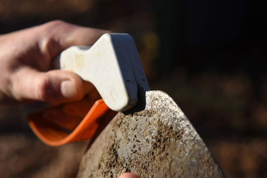 AccuSharp is one of many products for sharpening tools with a straight edge like shovels, trowels, hoes ect. The sharpener is run across the business end of a shovel in this photo to give it a good edge.