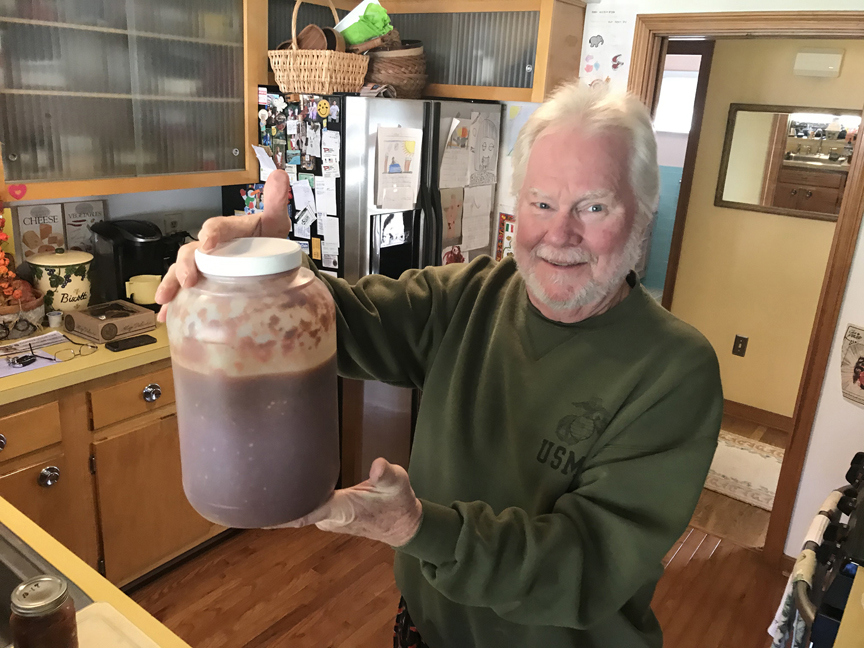 Dave Taiclet of Ross shows off a huge jar of his famous hot pepper elixir.