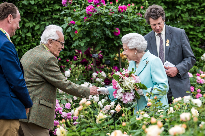 Britain's Queen Elizabeth II is greeted by David C. H. Austin, both then 90 years old, at the David Austin Roses garden at the 2016 Chelsea Flower Show in London on May 23, 2016. Behind Mr. Austin is his son David J. C. Austin, managing director of David Austin Roses.