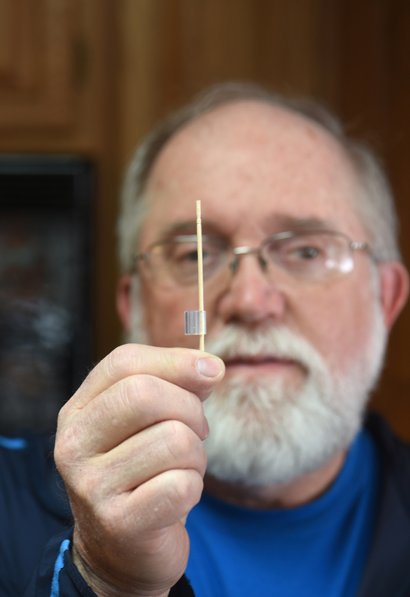 Rich Gebrosky holds a grafting clip with a small dowel rod, which acts as a stake to help support grafted tomatoes.